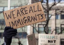 "Cardboard protest sign held up by a gloved hand reading, ""We are all immigrants"""