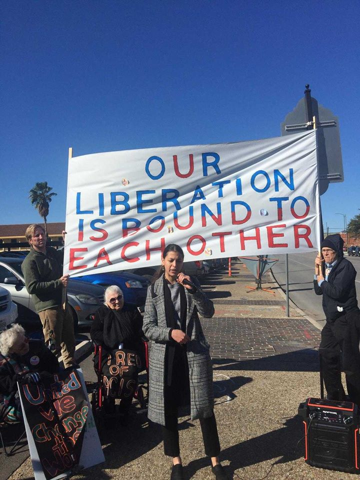 """Protest speaker with banner which says """"OUR LIBERATION IS BOUND TO EACH OTHER"""""""